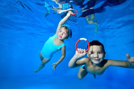 Happy little children, a boy and a girl, play and have fun under the water in the childrens pool. They swim with their eyes open and collect toys from the bottom. Close up. Concept. Horizontal view.