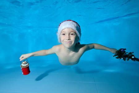 A happy little boy swims and poses for the camera underwater in the pool with Christmas gifts in his hands on a blue background in a red Santa Claus hat. Portrait. Horizontal orientation of the image.