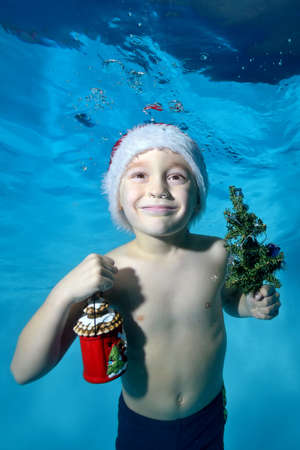 Portrait of a little boy in a red Santa Claus hat with a new year's gift in his hand and a small Christmas tree, who poses under water on a blue background. Vertical orientation of the photo.