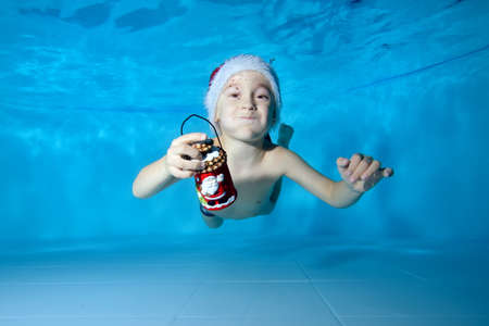 Funny baby swims and plays underwater in the pool with a Christmas toy in his hands in a red Santa hat on a blue background. Portrait. Horizontal orientation of the image. Stok Fotoğraf