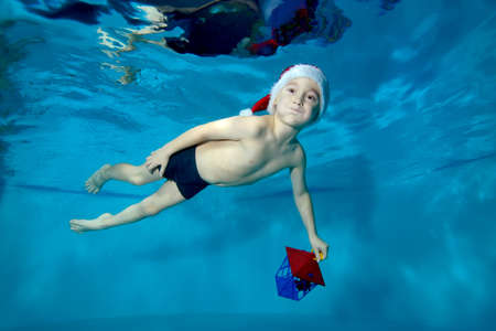 Funny child, boy, swims underwater in the pool in a red Santa hat with a toy in his hand. Portrait. Concept. Horizontal orientation of the photo.