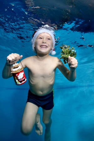 Laughing little boy swims and plays underwater in the pool in a red Santa hat with Christmas gifts in hand on a blue background. Portrait. Vertical orientation of the photo.