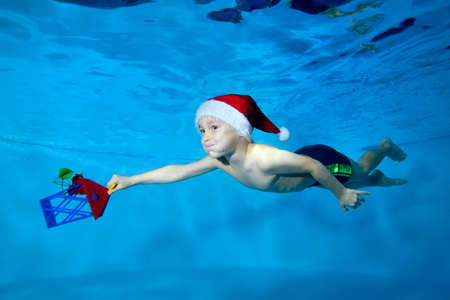A smiling little boy swims under the water in a red Santa hat with a Christmas toy in his hand. Portrait. Side view. Horizontal orientation of the photo.