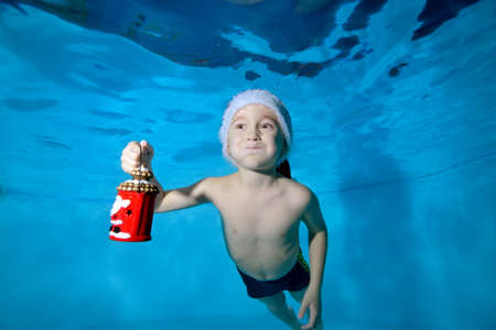 A cheerful little boy swims underwater in a pool with puffy cheeks and holds a Christmas toy in his hand. Portrait. Close up. Horizontal orientation of the image. Stok Fotoğraf