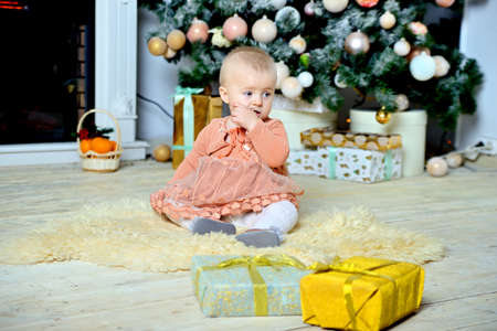 Pensive baby sitting on the floor near the Christmas tree with Christmas gifts.