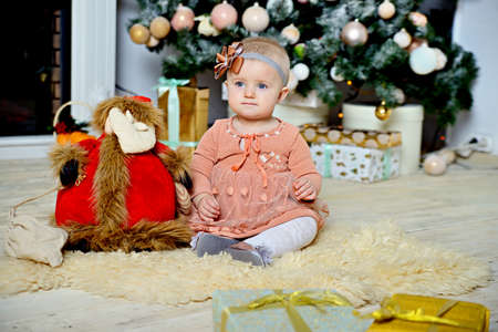 A little girl is sitting on a fur rug near a Christmas tree with Christmas toys.