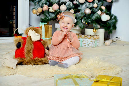 A smiling little girl sits on a fur rug near a Christmas tree with Christmas toys.