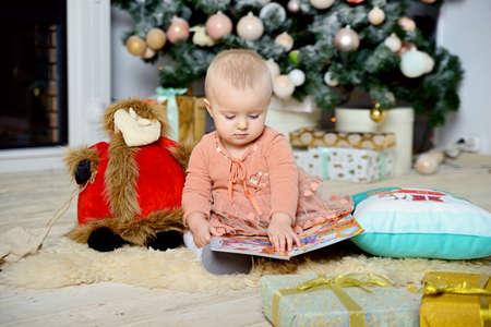 Little pensive girl sitting on the floor near the Christmas tree.