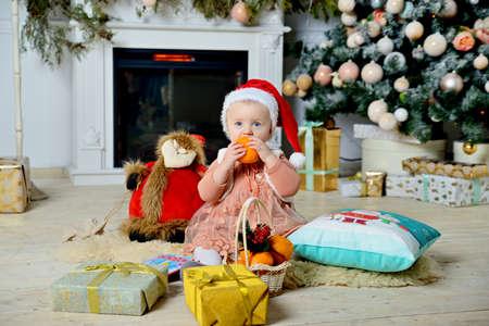Cute girl in a Christmas hat sitting on a rug near the Christmas tree. Stok Fotoğraf