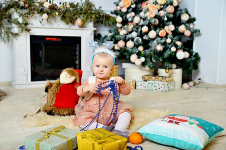 Cute girl on a fluffy rug near the Christmas tree and fireplace.