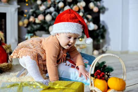 A beautiful little girl is sitting on a fluffy rug in a red Christmas hat near the Christmas tree. Stok Fotoğraf