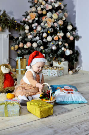 Cute baby in a Christmas hat near the Christmas tree. Stok Fotoğraf