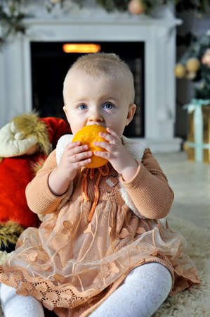 Funny little baby sitting on a fluffy carpet with toys.