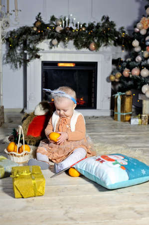 Beautiful little girl sitting on the carpet near the Christmas fireplace and Christmas tree.