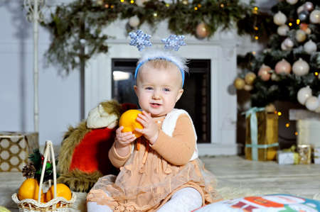 Cheerful girl sitting on a fluffy carpet near the Christmas fireplace and Christmas tree.