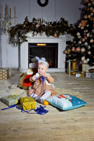 A little girl sitting on the carpet near the new years fireplace and Christmas tree. Stok Fotoğraf
