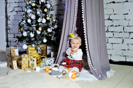 A smiling child playing on the carpet near the Christmas tree with gifts. Stok Fotoğraf