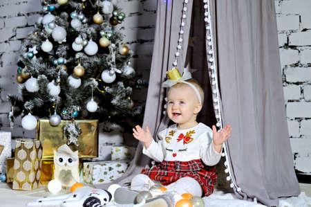 A smiling beautiful baby playing near the Christmas tree with gifts. Stok Fotoğraf