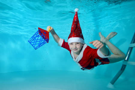 Close-up of a cheerful little boy in a Santa Claus costume underwater. He dives to the bottom of the pool with a new years gift. Active happy child. Healthy lifestyle. Swimming classes
