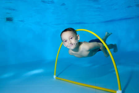 A little boy dives under the water in a childrens pool. It floats through the Hoop. Active happy child. Healthy lifestyle. Swimming lessons under the water. A family sport