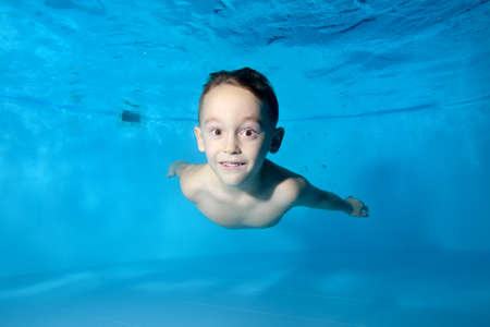 Portrait of a beautiful athletic boy underwater in the pool. Fun dives under the water. Swimming classes. Bodily exercises. Healthy lifestyle Stok Fotoğraf