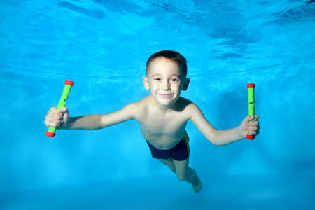 Portrait of a beautiful boy at the bottom of a childrens pool. He smiles and looks into the camera frame. Fun dives underwater. Active happy child. Swimming classes. Bodily exercises