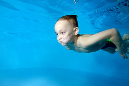 Photo of a little boy in class underwater at the bottom of a childrens pool. Active happy child. Healthy lifestyle. Swimming lessons under the water. A family sport Stok Fotoğraf
