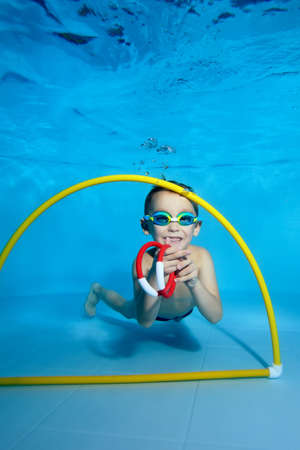 A picture of a cheerful boy in class underwater in a childrens pool. He swims through the Hoop, pulls out toys. Active happy child. Healthy lifestyle. Swimming lessons underwater. A family sport
