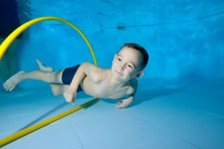 A beautiful little boy is swimming underwater in a childrens pool. He swims through the Hoop, pulls out toys. Active happy child. Healthy lifestyle. Swimming lessons under the water. A family sport