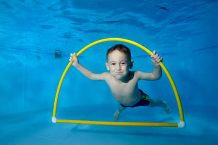Portrait of a smiling boy underwater in a childrens pool. He swims through the Hoop, pulls out toys. Active happy child. Healthy lifestyle. Swimming lessons under the water. A family sport