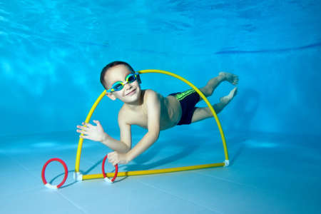 A beautiful little boy dives underwater in a childrens pool. He swims through the Hoop, pulls out toys. Active happy child. Healthy lifestyle. Swimming lessons under the water. A family sport