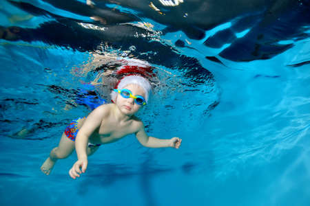 Portrait of a little boy in a Christmas hat and glasses in a pool under water. He looks at the camera. Baby learns to dive. Swimming lessons with a child. Healthy lifestyle. Horizontal orientation