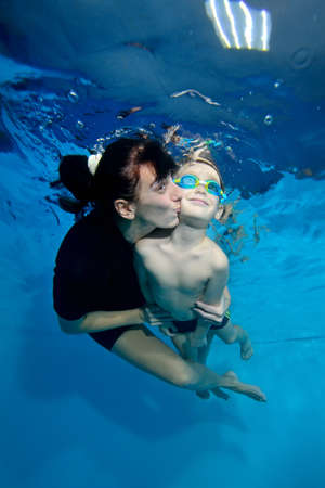 A beautiful little boy and his mother are swimming together under the water. She kisses him gently on the cheek. Active happy child. Family sports lessons. Healthy lifestyle Stok Fotoğraf