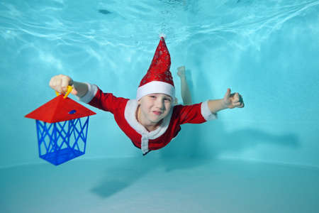 Beautiful boy underwater in Santa Claus costume at the bottom of the pool. He is holding a new years lantern. Swimming classes. Outdoor activity. Healthy lifestyle. The concept of the celebration Stok Fotoğraf
