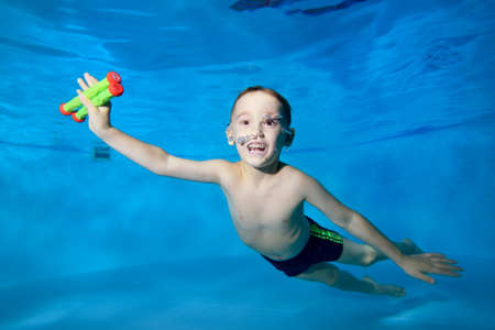 Laughing little boy fun dives to the bottom of the pool for toys. He smiles and looks into the camera frame. Fun dives under the water. Active happy child. Swimming classes. Healthy lifestyle
