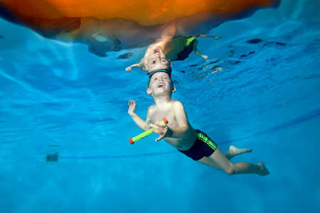 A picture of a little boy in class underwater in a childrens pool. He swims through the Hoop, pulls out toys. Active happy child. Healthy lifestyle. Swimming lessons under the water. A family sport