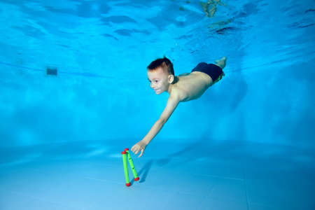 Cute athletic boy dives to the bottom of the pool for a toy. Fun dives underwater. Active happy child. Swimming classes. Bodily exercises. Healthy lifestyle Stok Fotoğraf