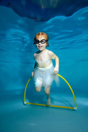 Frame with a little girl underwater in a childrens pool. Baby swims through the Hoop. Swimming lessons with a child. Healthy lifestyle. Horizontal orientation. The concept of the celebration Stok Fotoğraf