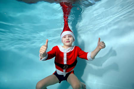 A picture of a boy smiling underwater in a Santa Claus costume in the pool. Active happy child. Healthy lifestyle. A swimming school. Athletics. The concept of the celebration