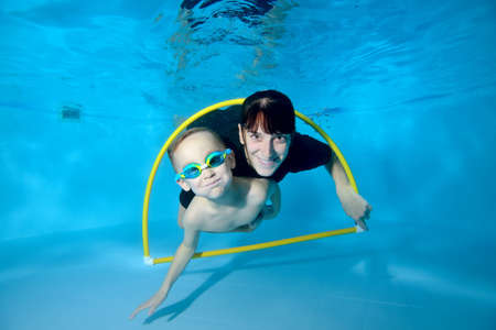 A happy toddler and a female trainer swim together underwater through a Hoop. They smile and look at the camera. Active happy child. Swimming lessons for small children. Healthy lifestyle