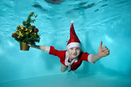 Underwater photo with a Christmas tree of a cheerful little boy in a Santa Claus costume. He dives to the bottom of the pool and gives a thumbs up. Active child. Healthy lifestyle Stok Fotoğraf