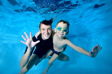 Portrait of a beautiful boy and his coach underwater. They smile and look at the camera. Active happy child. Swimming lessons for small children. Healthy lifestyle