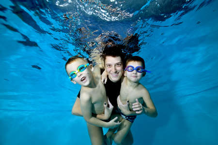 Two beautiful boys underwater with their mother. She hugs them tenderly. They smile and look at the camera. Active happy children. Healthy lifestyle. Swimming lessons under the water. Family sports Stok Fotoğraf