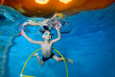 Portrait of a little boy in class underwater in a childrens pool. He swims through the Hoop, pulls out toys. Active happy child. Healthy lifestyle. Swimming lessons under the water. A family sport Stok Fotoğraf
