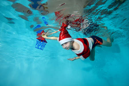 A beautiful boy is swimming underwater in a Santa Claus costume in the pool. He holds a new years lantern in his hand. Swimming classes. Outdoor activity. The concept of the celebration