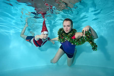 Portrait of a cute boy and a beautiful girl underwater in a Santa Claus costume in the pool. Classes with a coach. Healthy lifestyle. A swimming school. The concept of the celebration
