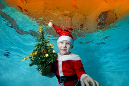 Portrait of a beautiful boy underwater in a Santa Claus costume at the bottom of the pool. He is holding a Christmas tree. Outdoor activity. Healthy lifestyle. The concept of the celebration