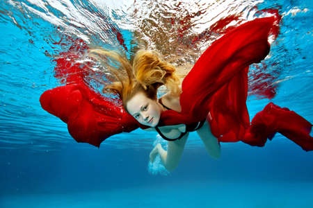 A cute girl is relaxing and having fun in the outdoor pool on a summer day. She dives under the water and swims with a red cloth in her hands with her hair flying. Portrait. Underwater photography. Stock Photo