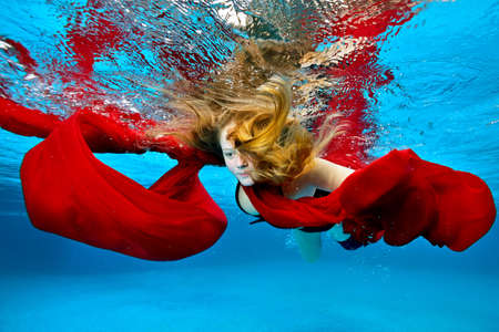 A creative portrait of a girl who swims underwater in a pool with a red cloth, arms outstretched like a bird, on a blue background. The concept. Underwater photography. Wide angle. Stock Photo