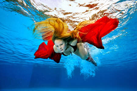 A lifeguard girl with long hair dives under the water and swims with a red cloth in her hands on a bright sunny day. Portrait. Underwater photography. Bottom view. Horizontal orientation.
